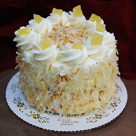 Three Layers Of Vanilla Sponge Cake Are Filled With Rum Flavored Whipped Cream And Pineapple Covered With Toasted Coconut And Garnished With Dried